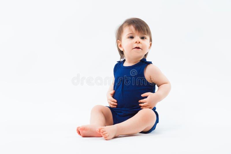Милая смешная малая усмехаясь девушка сидя в студии представляя на белой предпосылке стоковое изображение rf