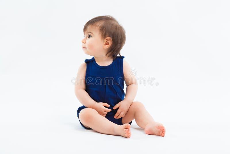 Милая смешная малая усмехаясь девушка сидя в студии представляя на белой предпосылке стоковые изображения