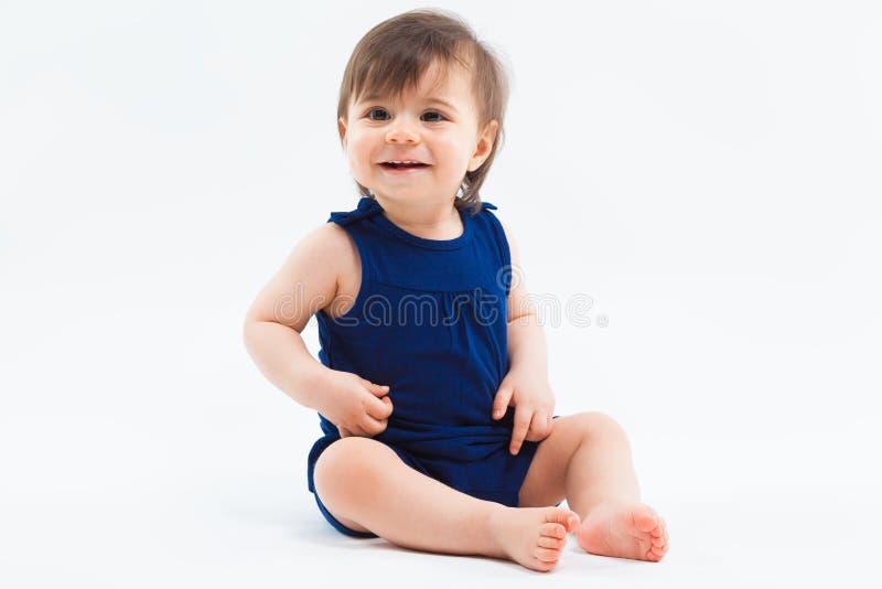 Милая смешная малая усмехаясь девушка сидя в студии представляя на белой предпосылке стоковые фото