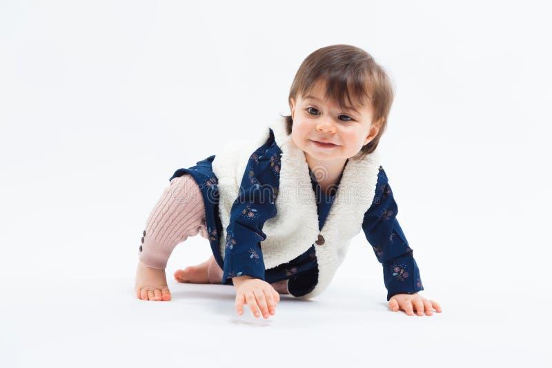 Милая смешная модная малая усмехаясь девушка сидя в студии представляя на белой предпосылке стоковое фото rf