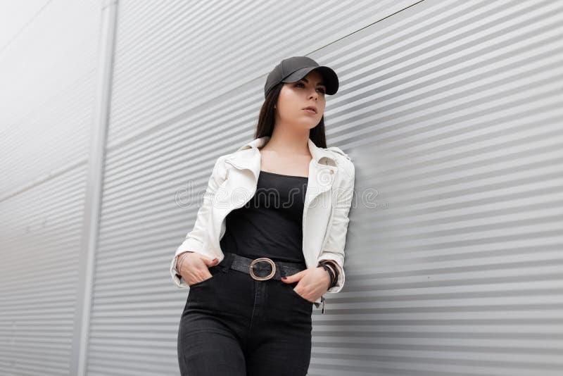 Милая современная молодая женщина в белой кожаной куртке в винтажных черных джинсах в стильной бейсбольной кепке отдыхает положен стоковые фотографии rf