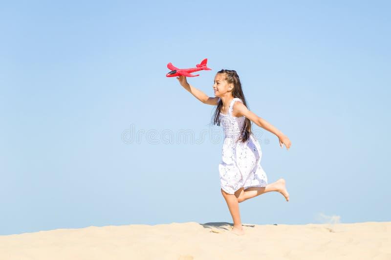 Милая счастливая маленькая девочка нося белое платье бежать на песчаном пляже морем и играя с красным t стоковые изображения rf