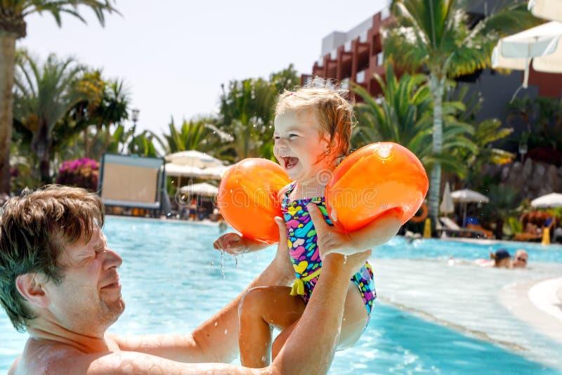 Милая счастливая маленькая девушка малыша и отец в бассейне и потеха иметь на семейных отдыхах в курорте гостиницы Здорово стоковая фотография