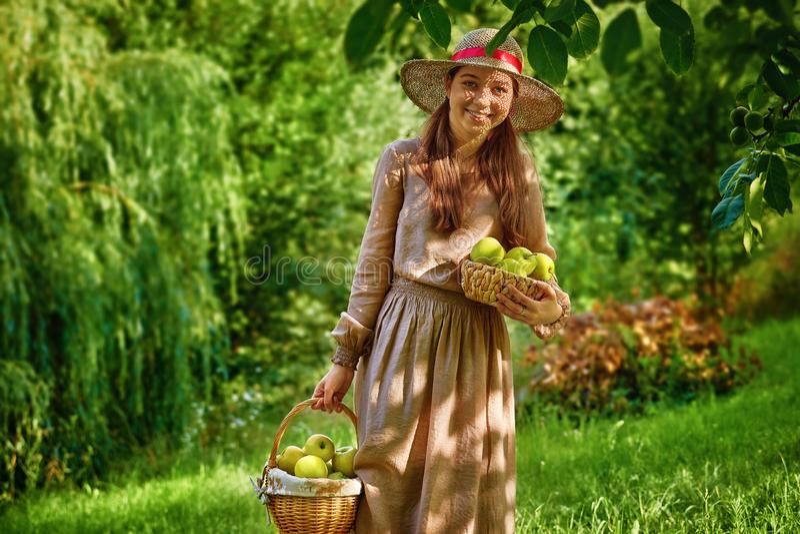 Милая усмехаясь девушка подростка в саде с корзиной яблок стоковые изображения