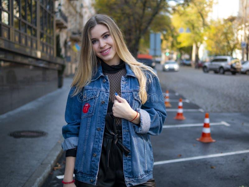 Милая усмехаясь девушка с роскошными волосами в куртке джинсовой ткани стоит в парковке для автомобилей на открытом воздухе стоковые изображения rf