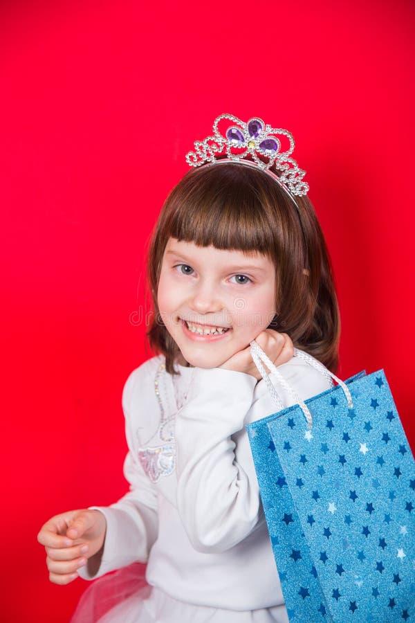 Милая усмехаясь маленькая девочка в костюме рождества снежинки держа праздничную сумку подарка в студии на красной предпосылке стоковая фотография