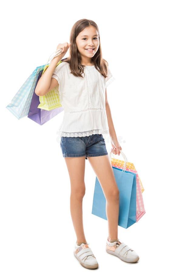 Милая усмехаясь маленькая девочка с хозяйственными сумками стоковые фотографии rf