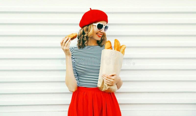 Милая усмехаясь молодая женщина нося красный круассан удерживания берета, бумажный мешок с длинным багетом белого хлеба на белизн стоковые фото
