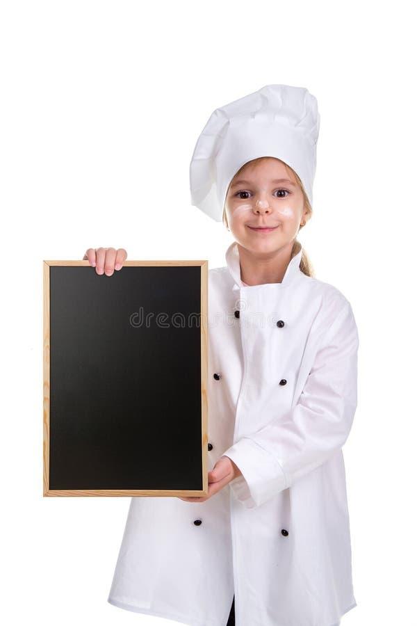 Милая усмехаясь форма шеф-повара девушки белая изолированная на белой предпосылке Девушка с floured стороной держа черноту меню п стоковая фотография