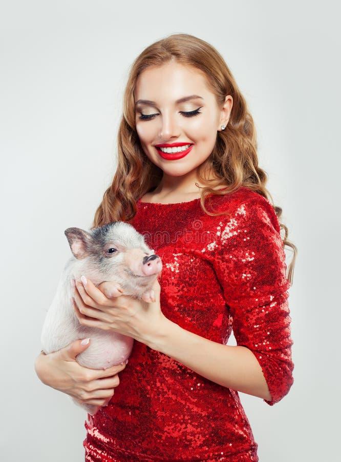 Милая фотомодель женщины в красном платье с меньшей свиньей стоковое изображение