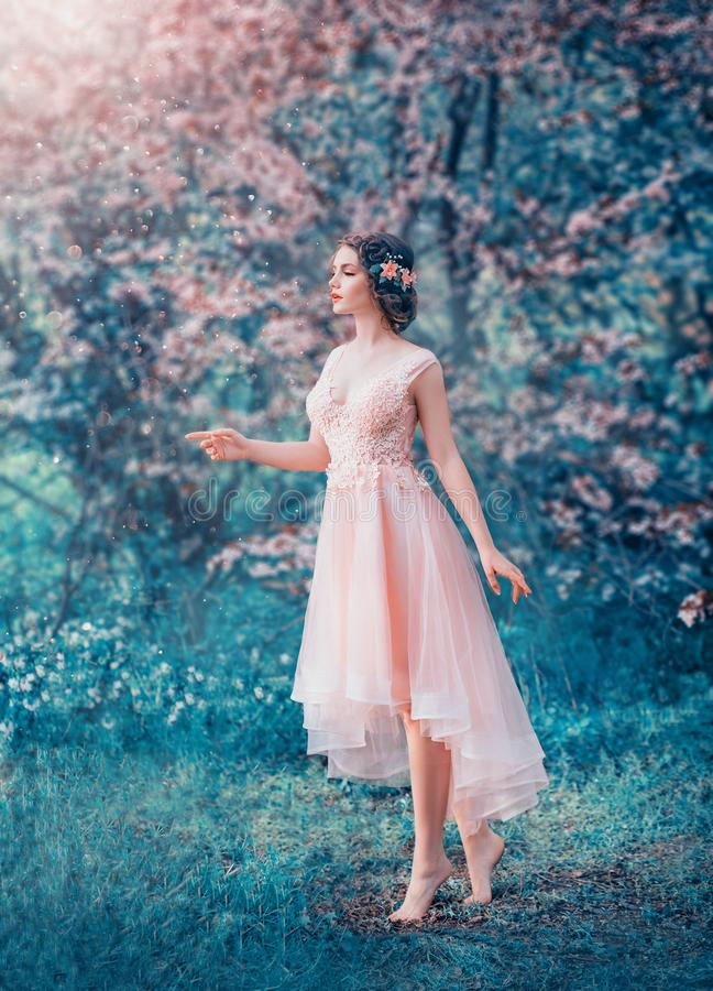 Милая худенькая девушка с заплетенными темными волосами в чувствительном элегантном платье персика, принцесса сказки в замороженн стоковые изображения rf