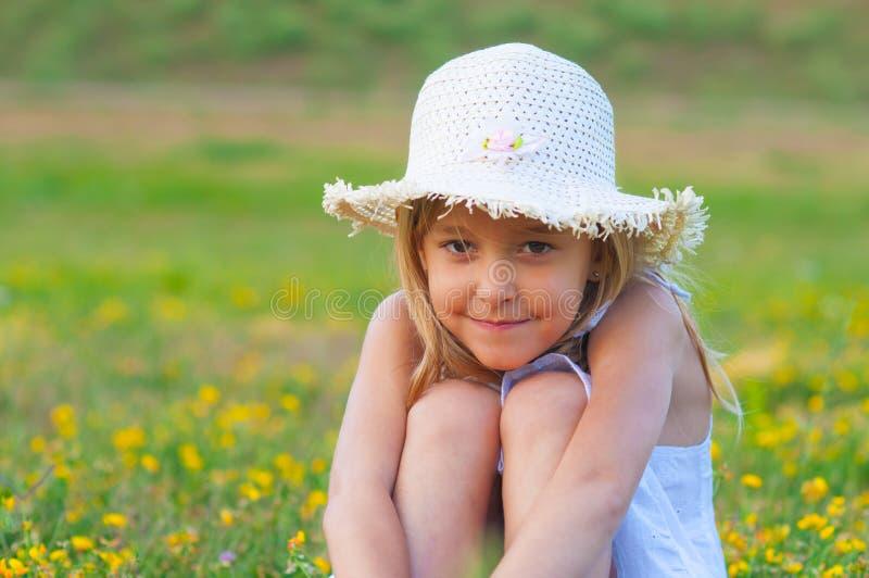Милая шикарная маленькая девочка сидя на лужке стоковые изображения