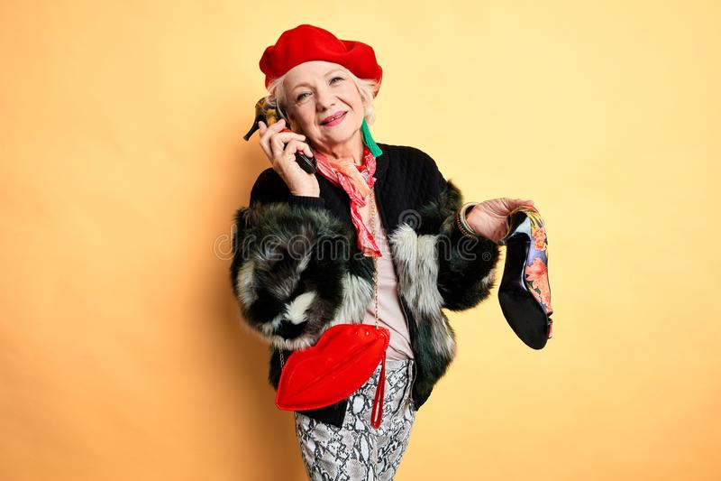 Милая элегантная женщина в ультрамодных одеждах разговаривая с другом стоковая фотография rf