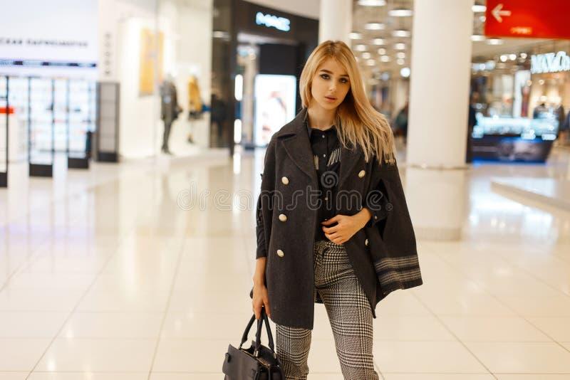 Милая элегантная молодая женщина в роскошном пальто в черной рубашке в винтажных серых checkered брюках с кожаной сумкой стоковые фото