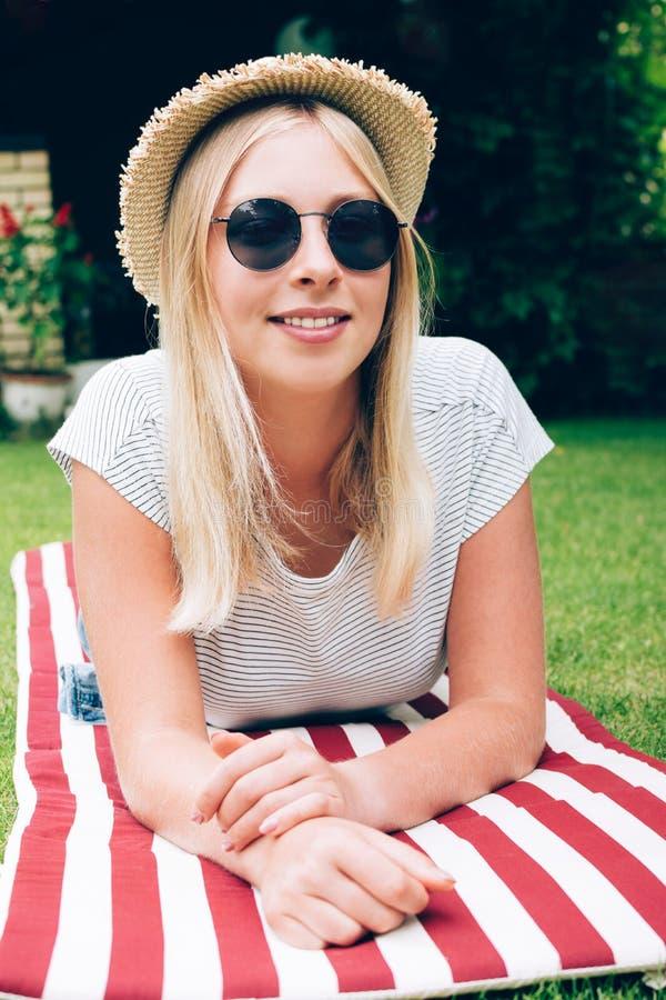 Миленькая блондинка-подросток лежит на зелёном газоне Поколение Z стоковые фотографии rf