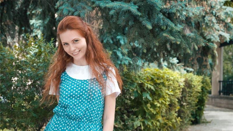 Миленькая красная девушка в кониферном парке стоковые изображения rf