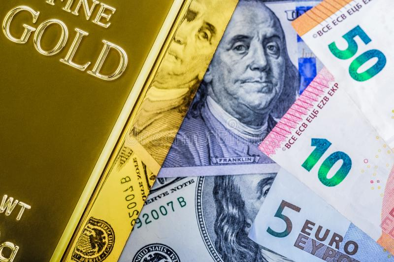 Миллиард слитка металла золота на предпосылке счетов доллара и евро стоковое фото rf