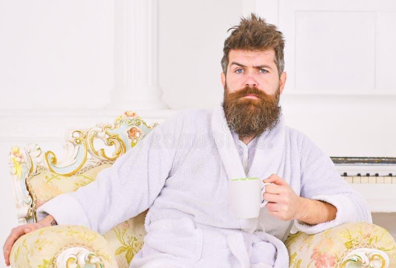 Миллионер наслаждаясь кофе утра Гай сидя в красивом стуле над белой предпосылкой Человек хмурясь и поднимая его стоковые фото