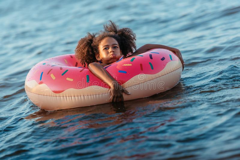 милое Афро-американское заплывание девушки в резиновом кольце и усмехаться стоковая фотография rf