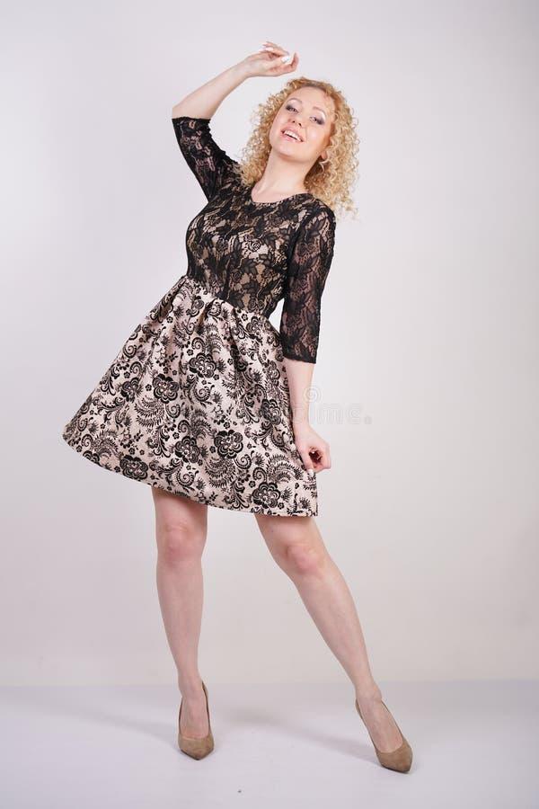 Милое белокурое платье города шнурка взрослой женщины нося и представлять на белой изолированной предпосылке девушка моды в модно стоковое фото