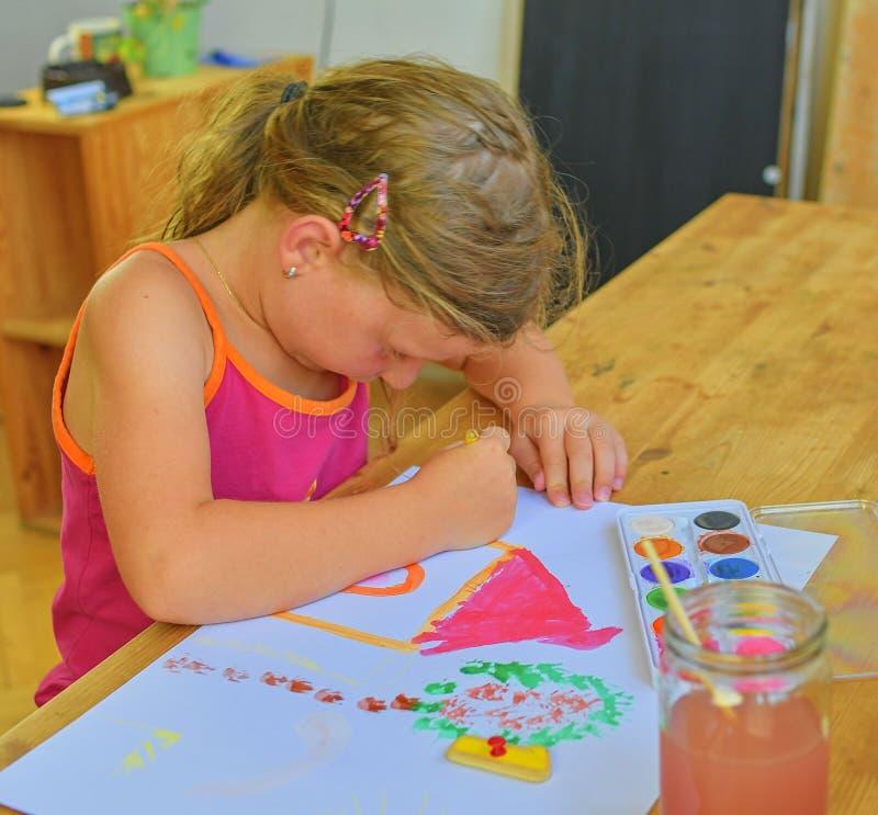 Милое изображение картины маленькой девочки дома Милая картина девушки с акварелями Концепция ипотеки Селективный фокус, малый DO стоковое фото