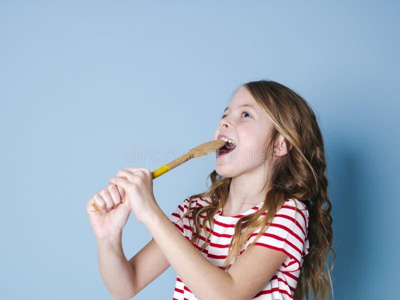Милое крутое и маленькая девочка используют варить ложку как микрофон и поют перед голубой предпосылкой и имеют много потеху стоковые фотографии rf