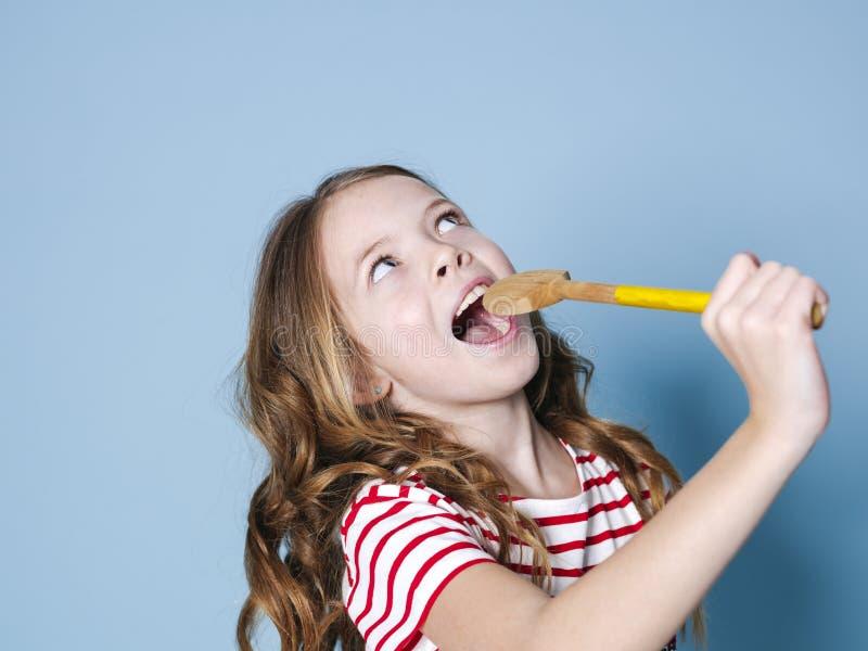 Милое крутое и маленькая девочка используют варить ложку как микрофон и поют перед голубой предпосылкой и имеют много потеху стоковые изображения rf