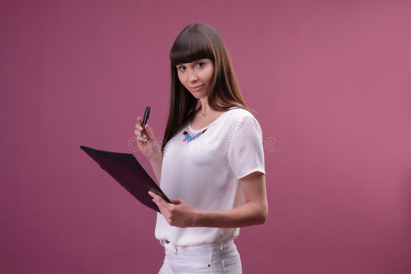 Милое молодое красивое положение женщины, сочинительство, примечания взятия, держащ организатор учебника в руке и ручке стоковое изображение rf