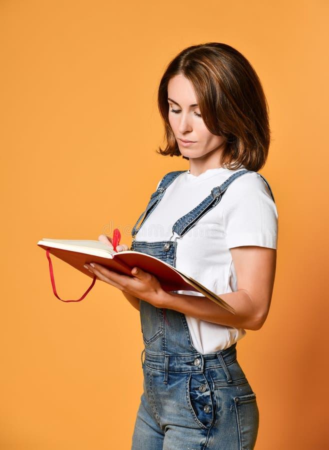 Милое молодое красивое положение женщины, сочинительство, примечания взятия, держа организатор тетради учебника в руке и ручке стоковые фото