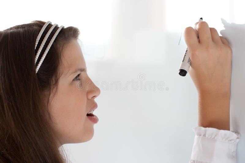 милое сочинительство whiteboard школьницы письма стоковая фотография