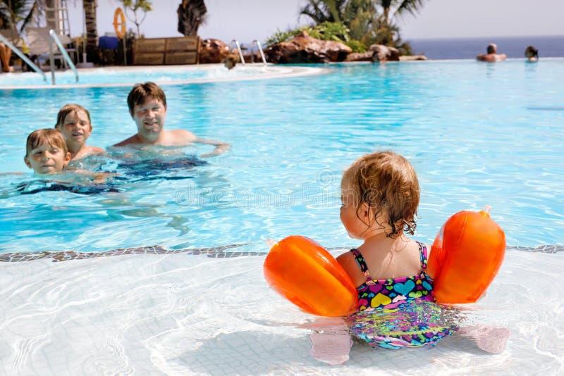 Милое счастливое маленькое заплывание девушки малыша в бассейне и потеха иметь на семейных отдыхах в курорте гостиницы ребенок зд стоковое изображение rf