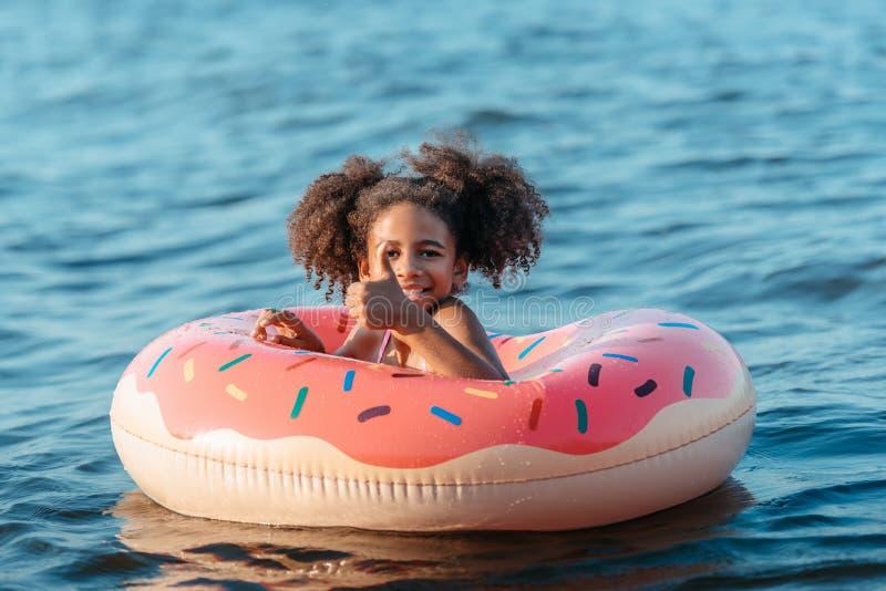 милое усмехаясь Афро-американское заплывание девушки в резиновом кольце и показе стоковая фотография rf