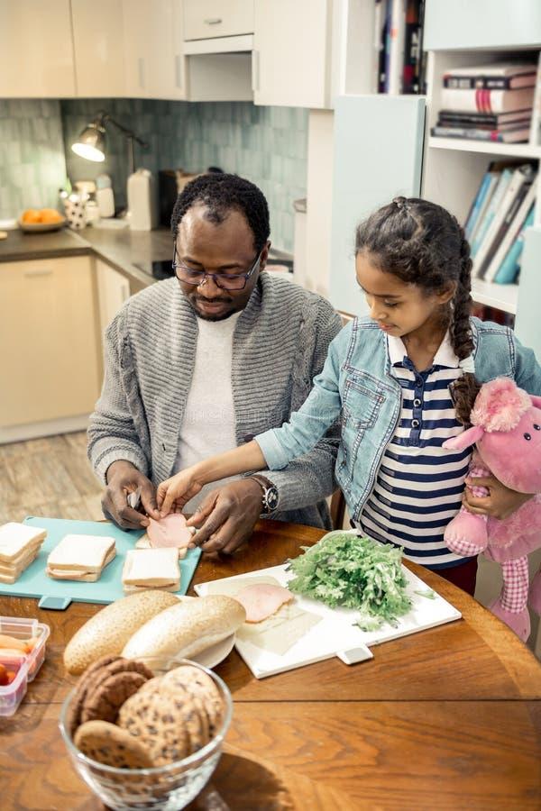 Милое чувство девушки радостное пока помогающ отцу делая сэндвичи стоковая фотография