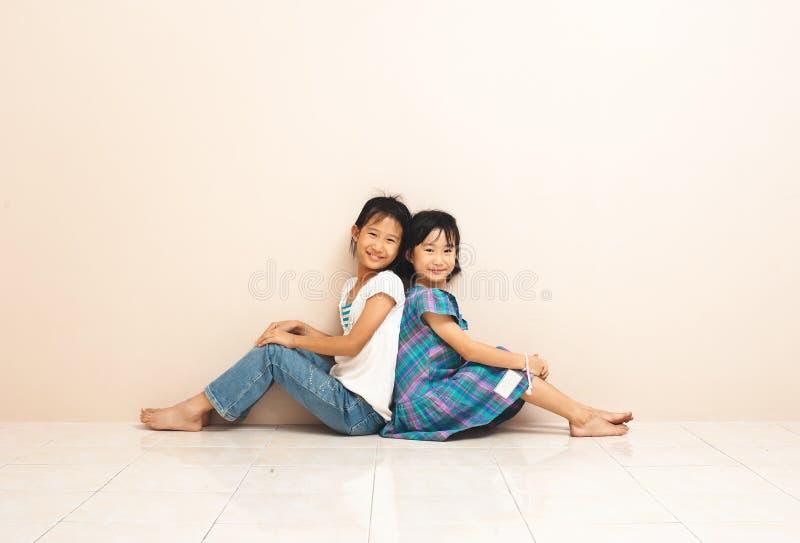 Милые азиатские братья сидеть и касаться один другого с их задними частями Прекрасные задушевные эмоции от детства стоковое фото