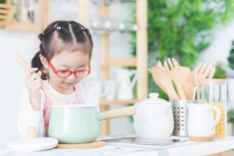 Милые азиатские девушки, тайские люди варят в кухне на его доме стоковые изображения rf
