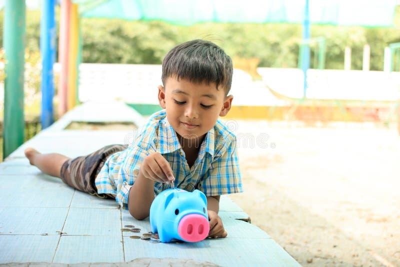 Милые азиатские деньги сбережений мальчика в копилке стоковое фото