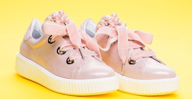 Милые ботинки на желтой предпосылке Обувь для девушек или женщин украшенных с жемчугом отбортовывает Пары бледного - розовая женщ стоковая фотография