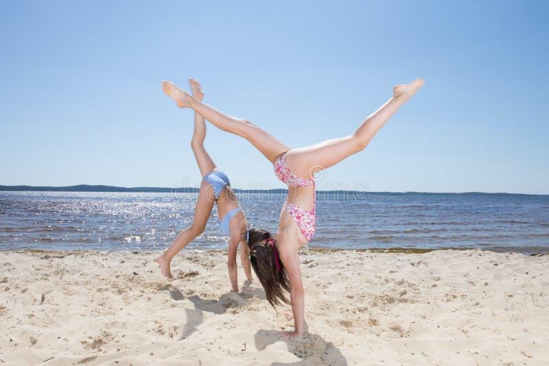 Милые девушки делая колесо телеги на пляже стоковое фото