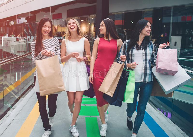 Милые девушки идут совместно в мол Они ходят по магазинам Молодые женщины имеют сумки в их руках смеяться над девушок стоковая фотография