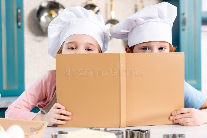 милые дети в шляпах шеф-повара держа поваренную книгу и смотреть стоковая фотография