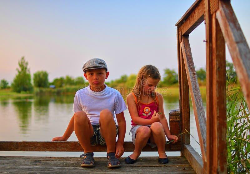 Милые дети, мальчик и девушка сидят на пристани в вечере лета отпрыски 2 Золотой час берегом озера Счастливый хи стоковое изображение