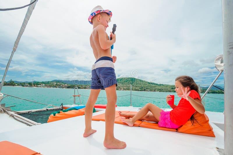 Милые дети на прогулке на яхте Мальчик играет гитару игрушки для его стоковые изображения rf