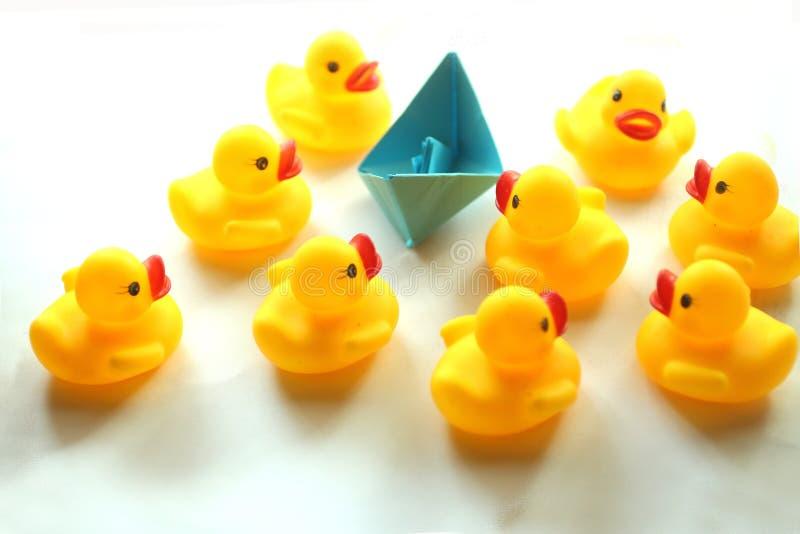 Милые желтые резиновые утки и голубой бумажный корабль стоковое фото rf