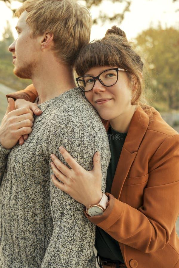 Милые красные с волосами пары человека и женщины в случайном обмундировании на дате Они идя в парк осени усмехаясь, обнимая и име стоковая фотография rf