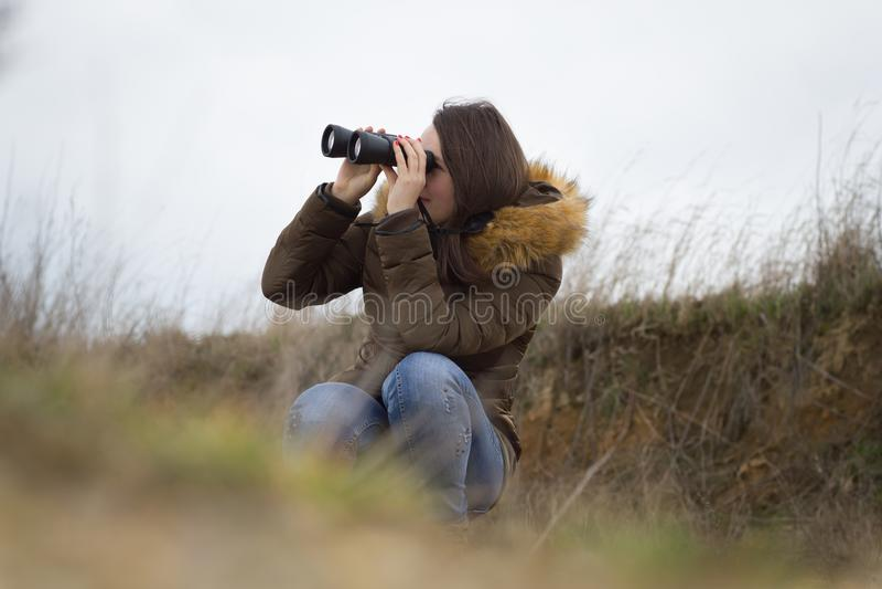 Милые маленькая девочка/женщина наблюдая вне телескопом t ornitology стоковые изображения rf