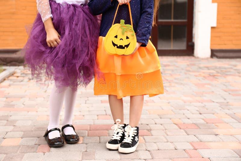 Милые маленькие девочки в костюмах хеллоуина фокус-или-обрабатывая outdoors стоковые изображения rf