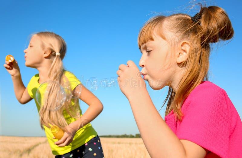 Милые маленькие девочки дуя пузыри мыла на солнечный день стоковое фото