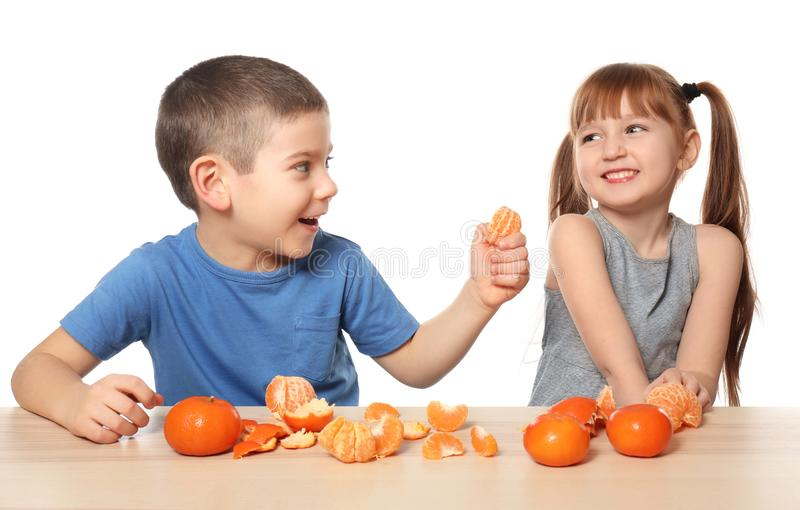 Милые маленькие дети есть цитрусовые фрукты на таблице на белой предпосылке стоковые изображения