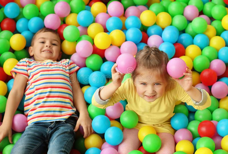 Милые маленькие дети играя в яме шарика на парке атракционов стоковая фотография