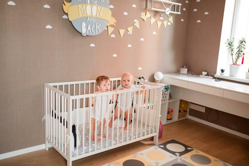 Милые маленькие младенцы смотря из кровати стоковое изображение